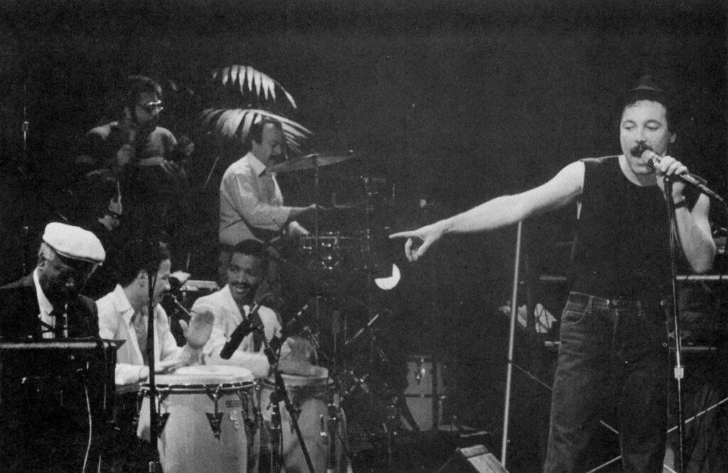 Rubén Blades во время выступления в Филлморе, Сан-Франциско, совместно с (по часовой стрелке слева): Armando Peraza, Karl Perazzo, Ralphy Irizarry, Orestes Vilato, Jesús Diaz и Bobby Allende. ©1987, René Castro.