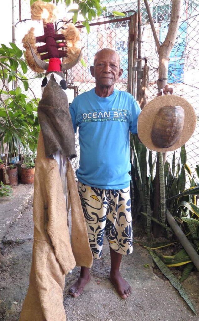 """Нальдо с мокондо - балахоном абакуа (еще не дошитым до конца), с семью понпонами и рогами козла. В его левой руке он держит """"ita muson"""", маленькую """"шляпу"""" Иреме, сделанную из панциря черепахи."""